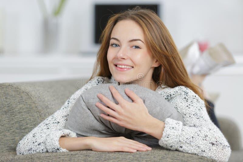Szczęśliwa młodej kobiety przytulenia szarość poduszka obraz stock