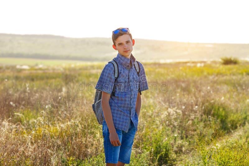 Szczęśliwa młody człowiek pozycja z plecakiem outdoors na słonecznym dniu zdjęcie royalty free