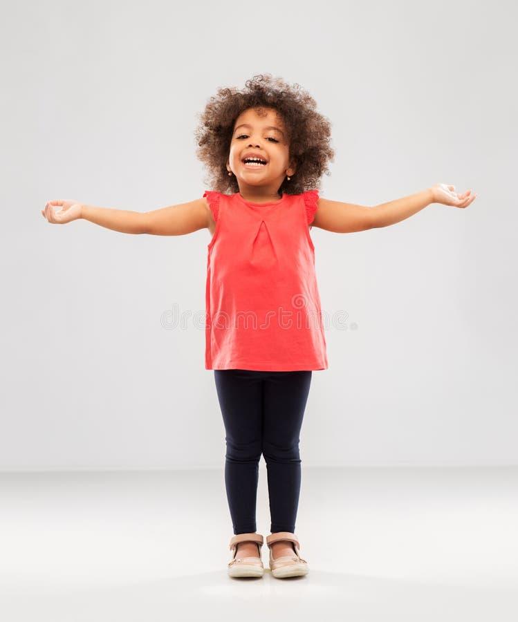 Szczęśliwa mała amerykanin afrykańskiego pochodzenia dziewczyna z rękami w oddaleniu fotografia stock