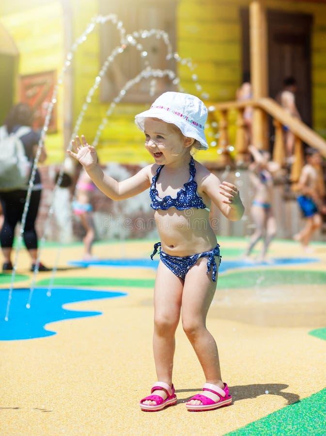 Szczęśliwa mała berbeć dziewczyna bawić się przez fontanny fotografia stock