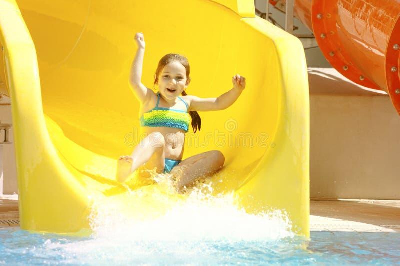 Szczęśliwa mała caucasian dziewczyna na waterslide woda park zdjęcie stock