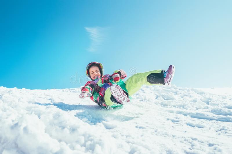 Szczęśliwa mała dziewczynka ślizga się puszek od śnieżnego skłonu Cieszyć się fotografia stock
