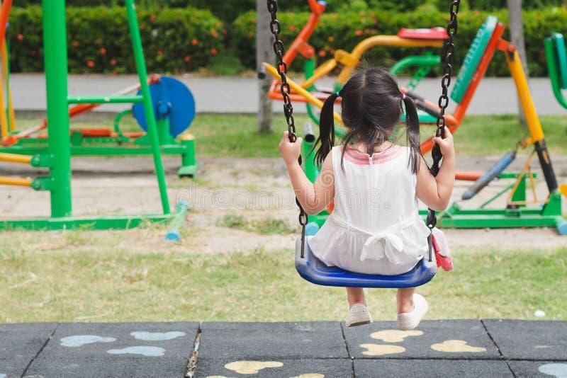 Szczęśliwa mała dziewczynka bawić się huśtawkę przy boiskiem Szczęśliwy, rodzina obrazy royalty free