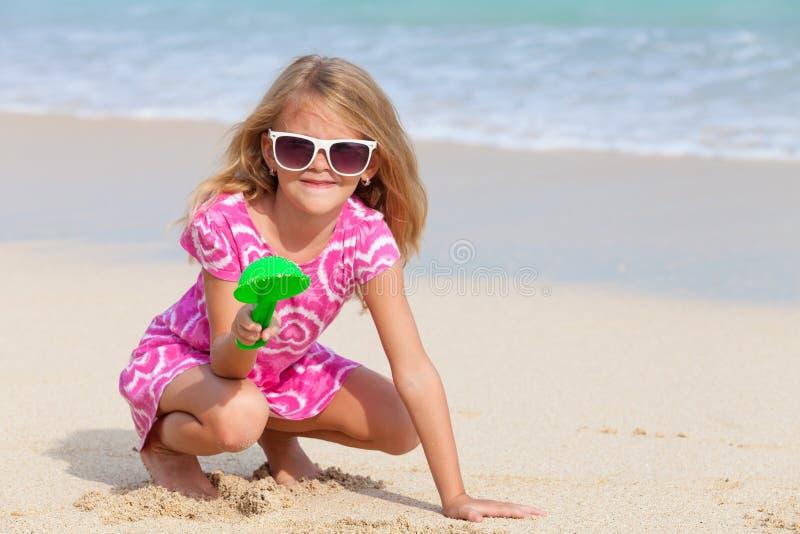 Szczęśliwa mała dziewczynka bawić się na plaży obraz stock