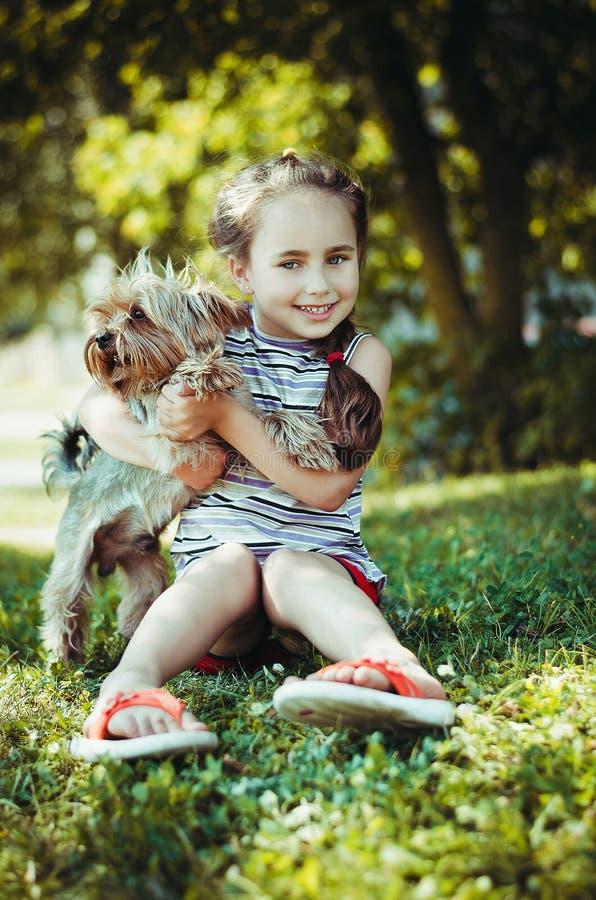 Szczęśliwa mała dziewczynka bawić się z psem obraz stock