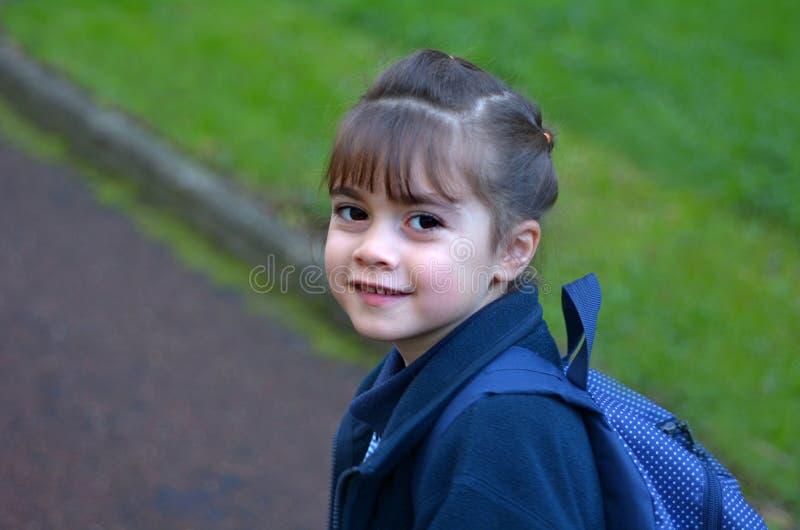 Szczęśliwa mała dziewczynka chodzi szkolny przyglądający nad jej shoulde z powrotem zdjęcia royalty free