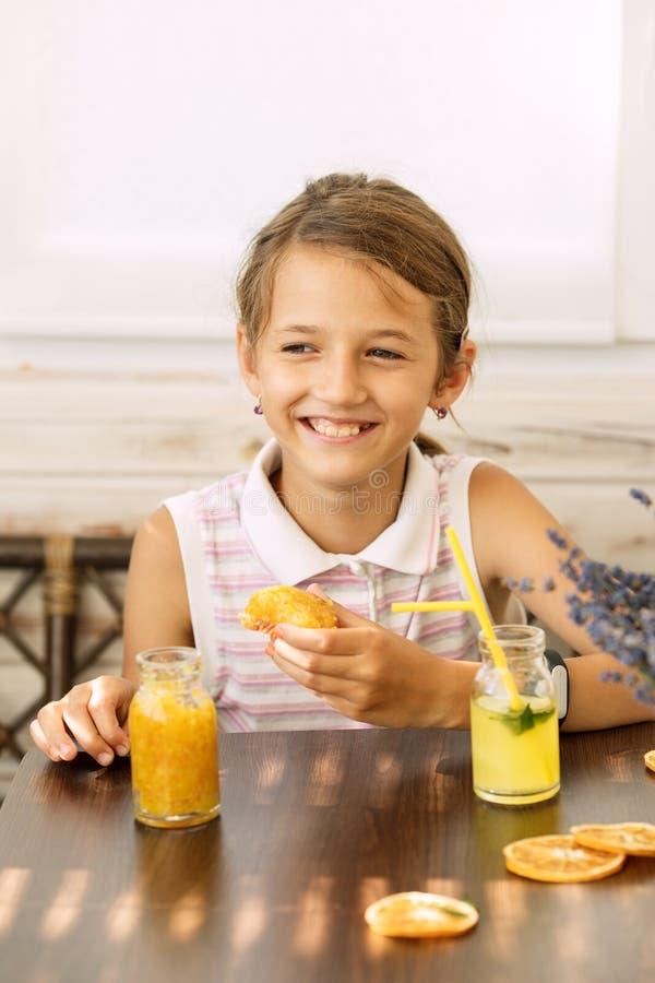 Szczęśliwa mała dziewczynka cieszy się i pije soku pomarańczowego obsiadanie szkolny wiek zdrową śniadaniową łasowanie kanapkę, o zdjęcia royalty free