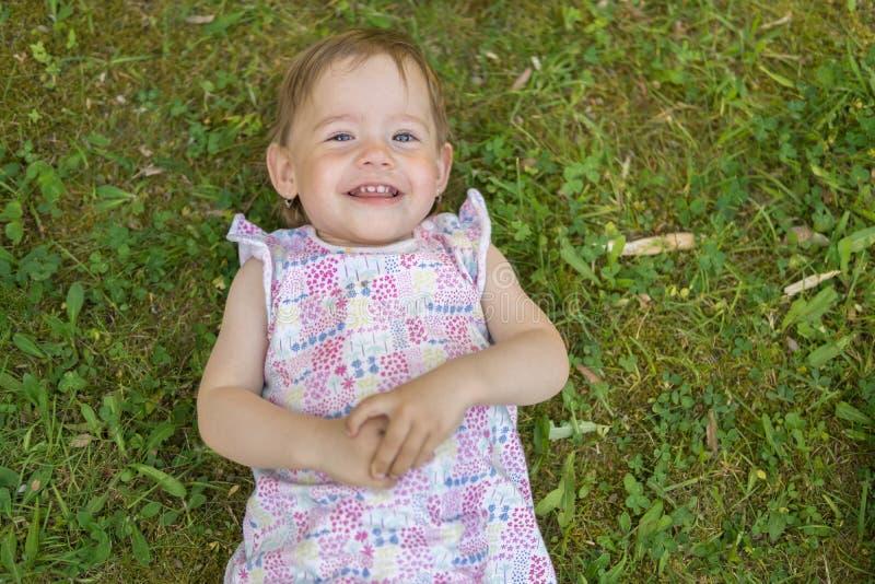 Szczęśliwa mała dziewczynka dziecko kłama na zielonej trawie w parku zdjęcie royalty free