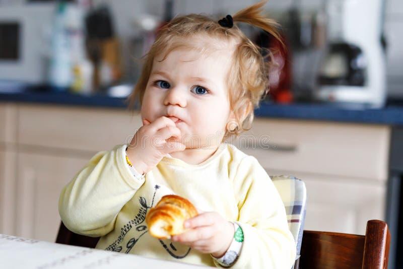 Szczęśliwa mała dziewczynka je świeżego croissant dla śniadania lub lunchu Dla dzieci zdrowy łasowanie obrazy stock