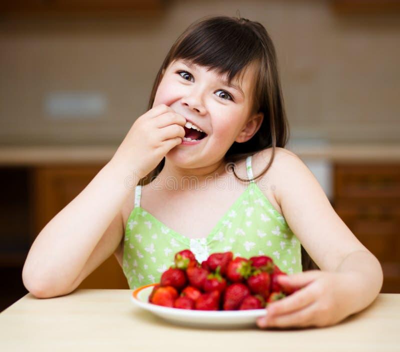 Szczęśliwa mała dziewczynka je truskawki obraz stock