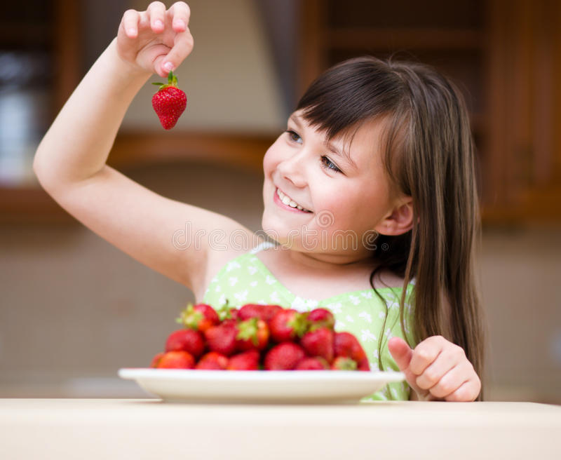 Szczęśliwa mała dziewczynka je truskawki zdjęcia stock