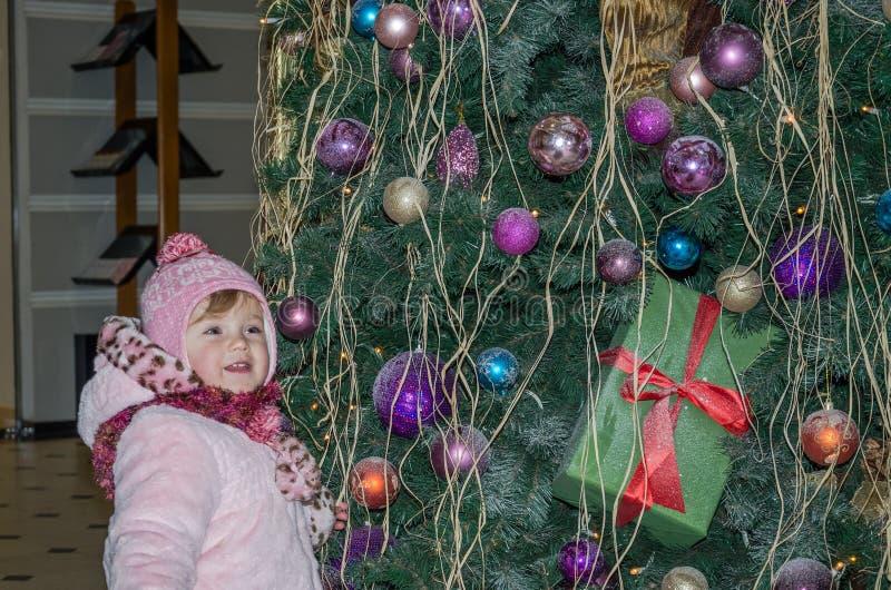 Szczęśliwa mała dziewczynka jest piękna w białym futerkowym żakiecie, kapelusz, szalik z zabawkami, girlandy i smi, blisko choink obrazy royalty free