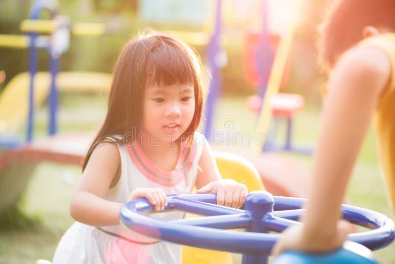 Szczęśliwa mała dziewczynka ma zabawę na boisku cieszy się huśtawkowego ri obrazy stock
