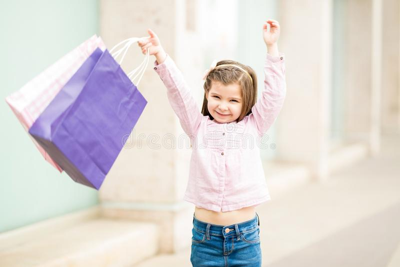 Szczęśliwa mała dziewczynka ma zabawę podczas gdy robiący zakupy obrazy royalty free