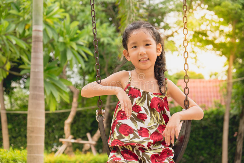 Szczęśliwa mała dziewczynka na huśtawce, uśmiechnięta twarz obraz stock