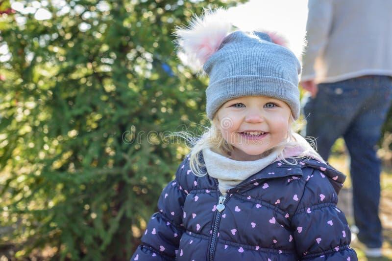 Szczęśliwa mała dziewczynka outside przy choinka udziałem w zimie obrazy royalty free