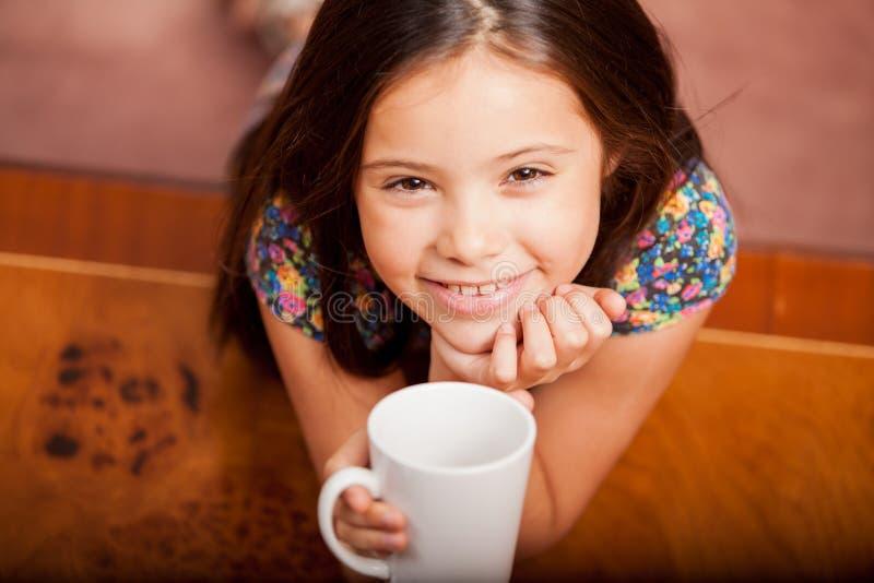Szczęśliwa mała dziewczynka pije herbaty obrazy royalty free