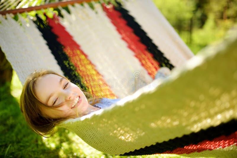Szczęśliwa mała dziewczynka relaksuje w hamaku na pięknym letnim dniu Śliczny dziecko ma zabawę w wiosna ogródzie zdjęcia royalty free