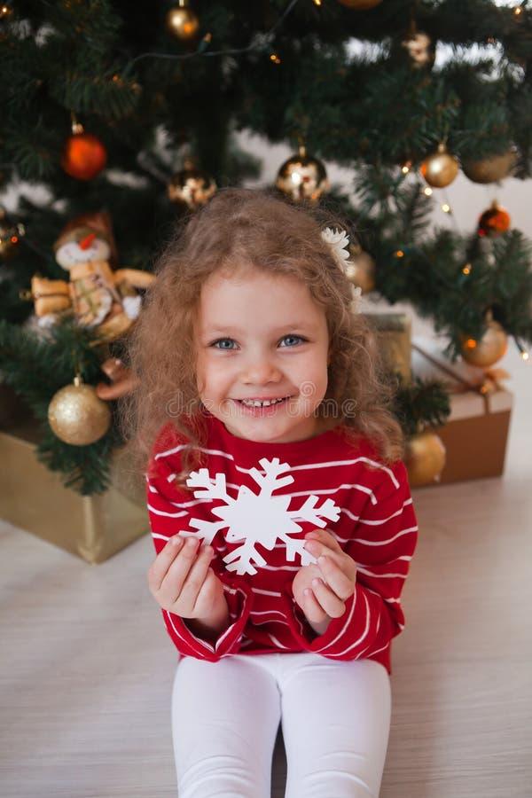 Szczęśliwa mała dziewczynka siedzi pod choinką i trzyma płatek śniegu obraz royalty free
