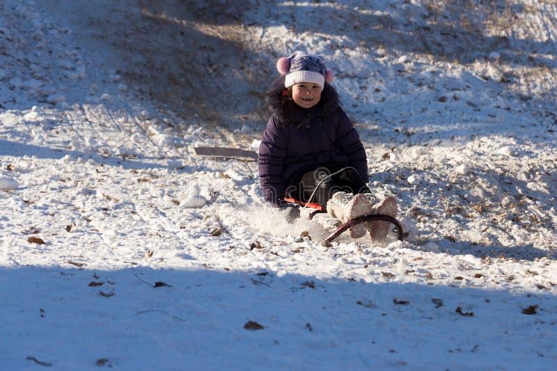 Szczęśliwa mała dziewczynka sledding na białym śnieżnym śniegu od wzgórza obrazy stock