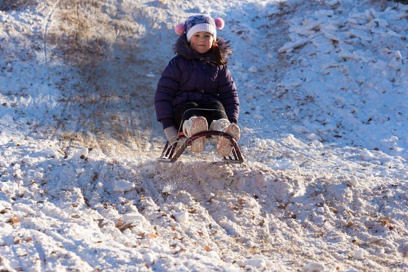 Szczęśliwa mała dziewczynka sledding na białym śnieżnym śniegu od wzgórza zdjęcia royalty free