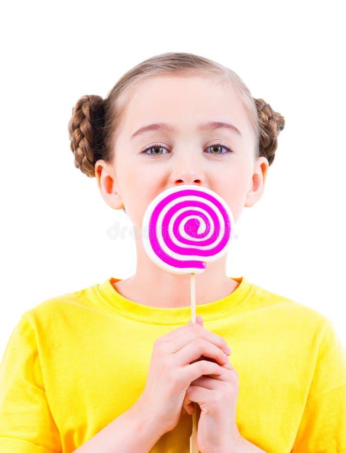 Szczęśliwa mała dziewczynka w żółtym koszulki łasowaniu barwił cukierek fotografia royalty free