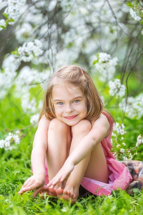 Szczęśliwa mała dziewczynka w czereśniowego okwitnięcia ogródzie fotografia royalty free