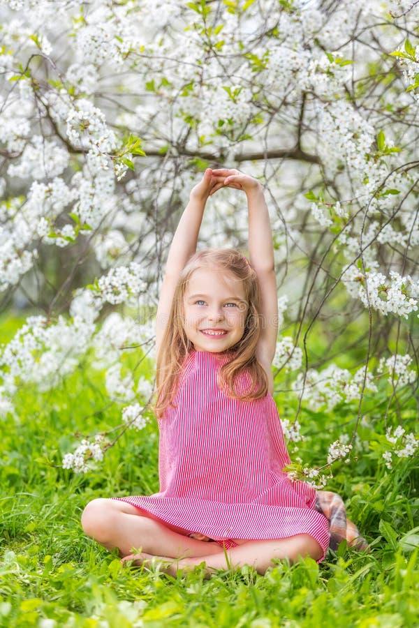 Szczęśliwa mała dziewczynka w czereśniowego okwitnięcia ogródzie zdjęcie stock