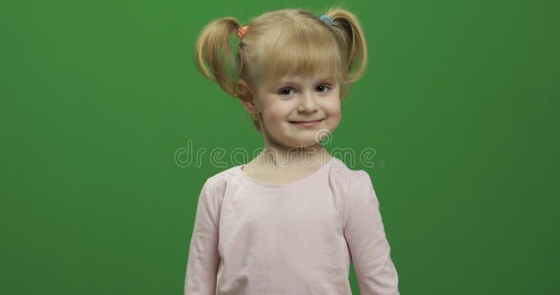 Szczęśliwa mała dziewczynka w różowej koszulce Śliczny blondynki dziecko robi twarzom zdjęcie royalty free