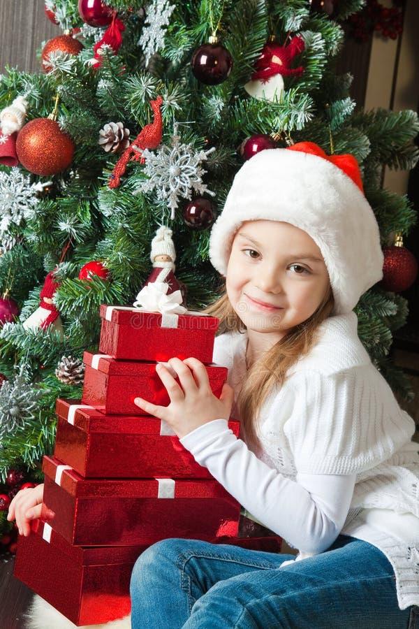 Szczęśliwa mała dziewczynka w Santa kapeluszu z prezentami zdjęcie royalty free
