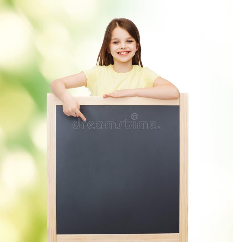 Szczęśliwa mała dziewczynka wskazuje palec blackboard obraz stock