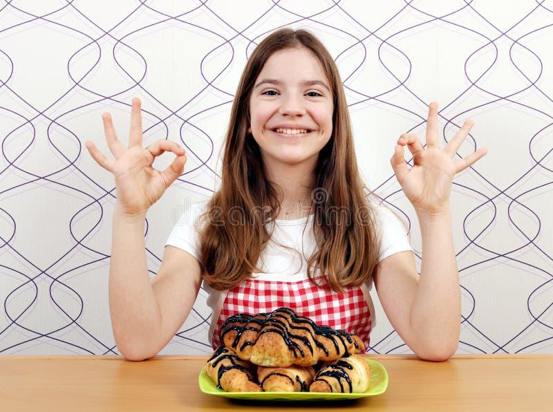 Szczęśliwa mała dziewczynka z croissant i ok ręką podpisuje obraz stock