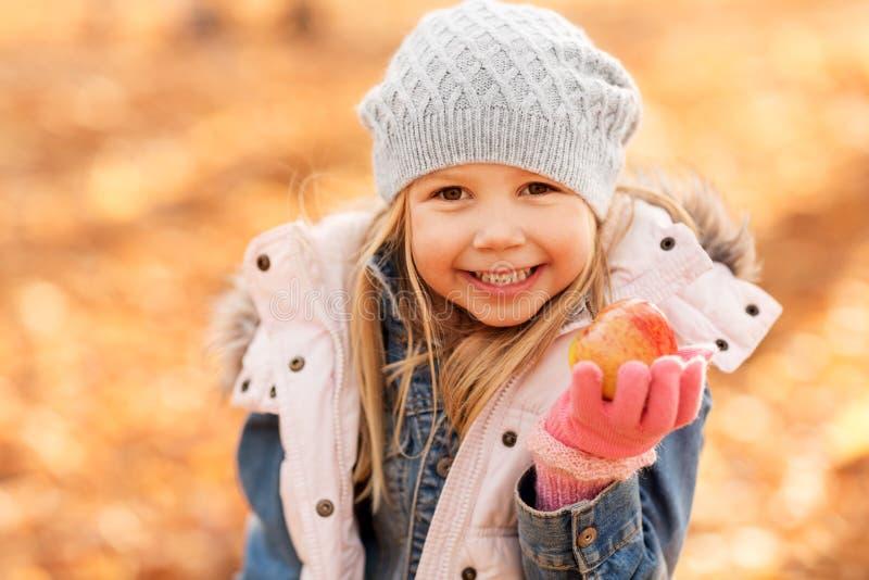 Szczęśliwa mała dziewczynka z jabłkiem przy jesień parkiem zdjęcie royalty free