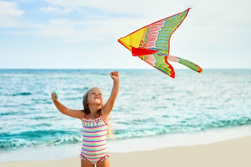 Szczęśliwa mała dziewczynka z latającą kanią na tropikalnej plaży zdjęcia royalty free