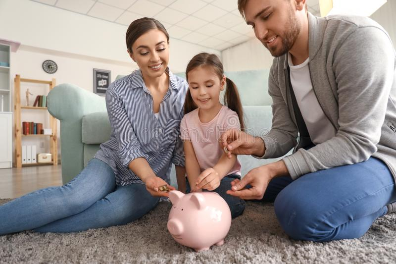 Szczęśliwa mała dziewczynka z ona rodzice siedzi na dywanie i stawia monetę w prosiątko banka indoors butelki poj?cia dolarowi pi zdjęcia stock