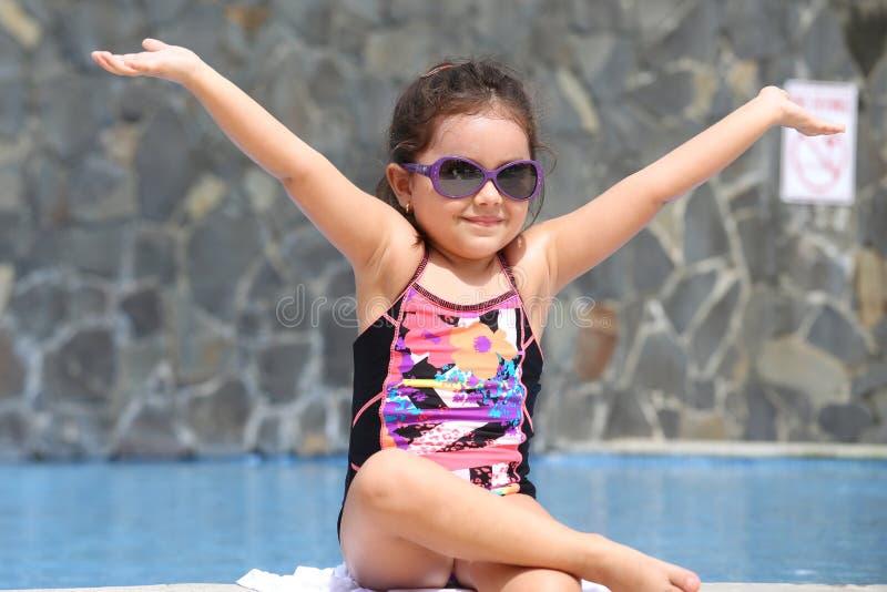 Szczęśliwa mała dziewczynka z otwartymi rękami na zewnątrz basenu zdjęcie royalty free