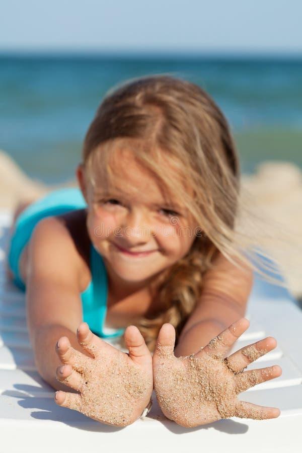 Szczęśliwa mała dziewczynka z piaskowatymi rękami na plaży obrazy royalty free