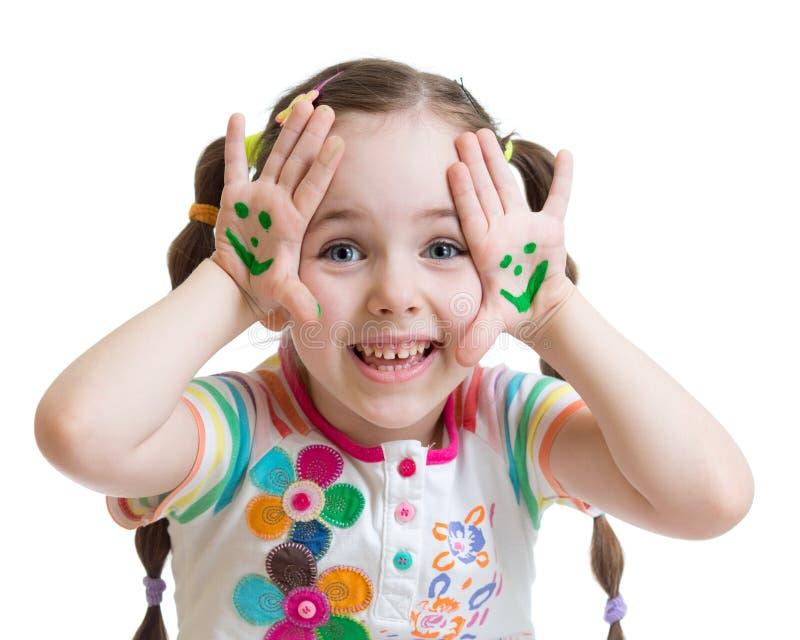 Szczęśliwa mała dziewczynka z smiley twarzami malował na jej palmach obrazy stock