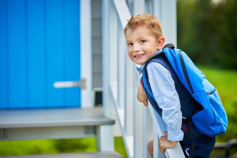 Szczęśliwa mała preschool dzieciak chłopiec z plecakiem pozuje outdoors fotografia royalty free