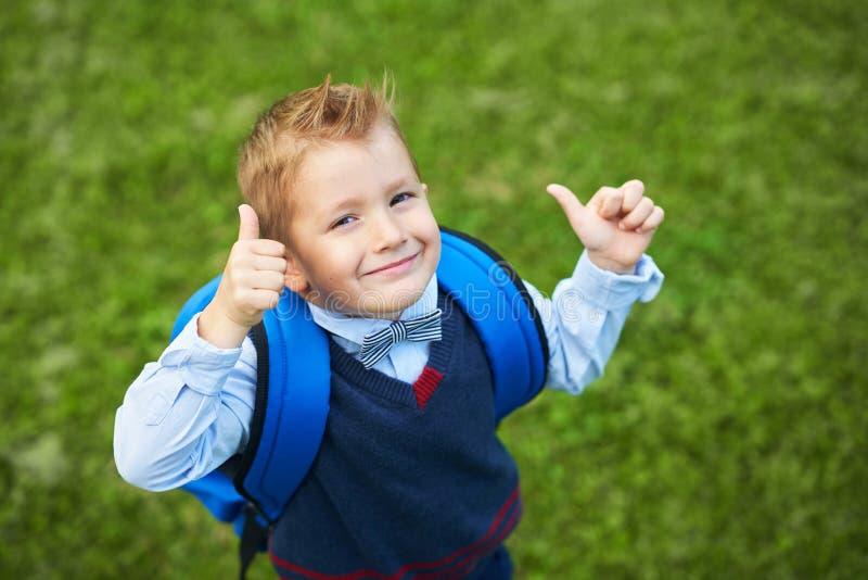 Szczęśliwa mała preschool dzieciak chłopiec z plecakiem pozuje outdoors zdjęcia stock
