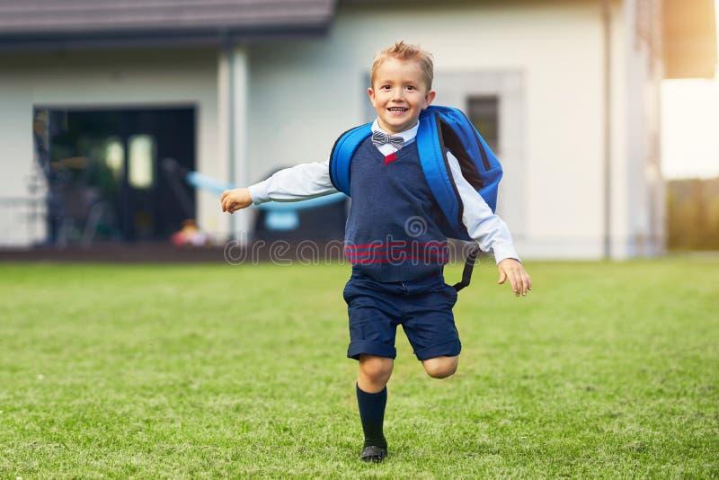 Szczęśliwa mała preschool dzieciak chłopiec z plecakiem pozuje outdoors zdjęcie stock