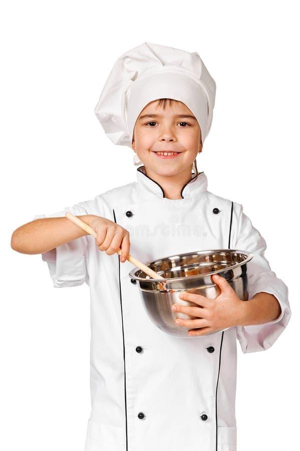 Szczęśliwa mała szef kuchni dziewczyna z kopyści dziewczyną ma zabawę robić ciastkom fotografia royalty free