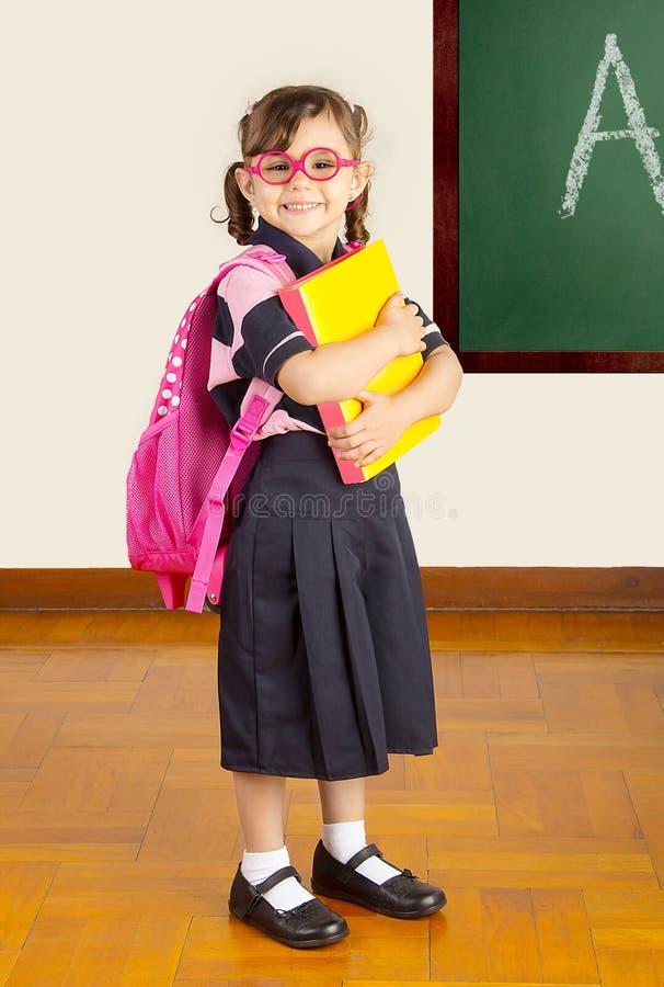 Szczęśliwa Mała Szkolna dziewczyna przy szkolną sala lekcyjną fotografia stock