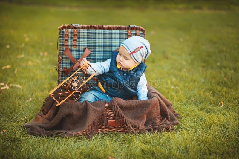Szczęśliwa małe dziecko chłopiec bawić się z samolot zabawką podczas gdy siedzący w walizce na zielonym jesień gazonie Dzieci cie zdjęcie royalty free
