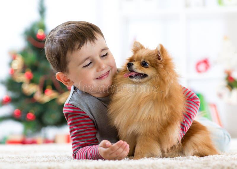 Szczęśliwa małe dziecko chłopiec, pies jako ich prezent przy bożymi narodzeniami i Bożenarodzeniowy wnętrze obraz royalty free