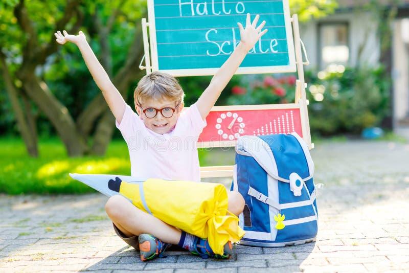 Szczęśliwa małe dziecko chłopiec siedzi biurkiem, plecak i satchel z szkłami zdjęcia stock