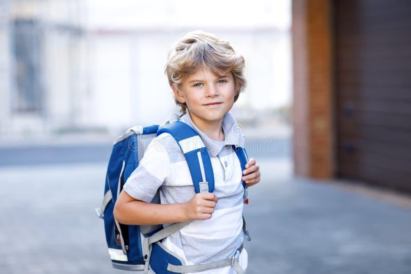 Szczęśliwa małe dziecko chłopiec z plecakiem lub satchel Schoolkid na sposobie szkoła Zdrowy uroczy dziecko outdoors na zdjęcia stock