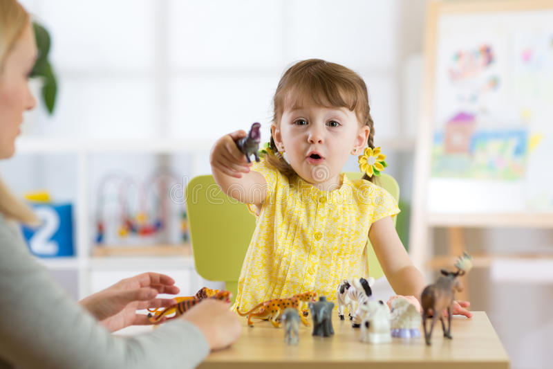 Szczęśliwa małe dziecko dziewczyna Uśmiechnięty dziecko berbeć bawić się zwierzęce zabawki lub dziecina w domu zdjęcie stock
