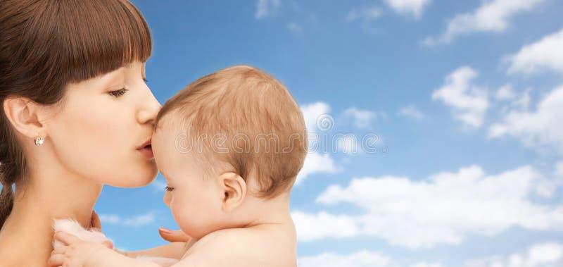 Szczęśliwa macierzysta całowanie chłopiec nad nieba tłem obraz royalty free