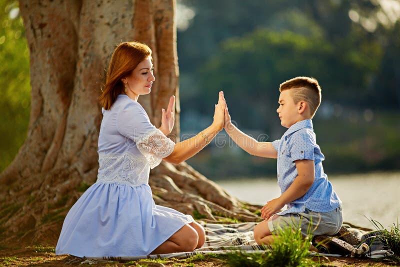Szczęśliwa mama i syn bawić się w parku w wiośnie Macierzysty opowiadać jej syn w parku obrazy stock